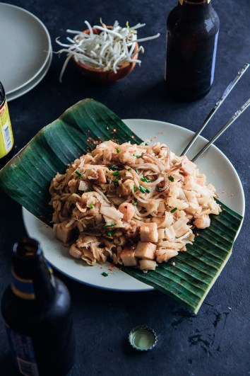 Char kuey teow Malaysian stir fried noodles on bamboo on a white plate on a black table with an open beer.