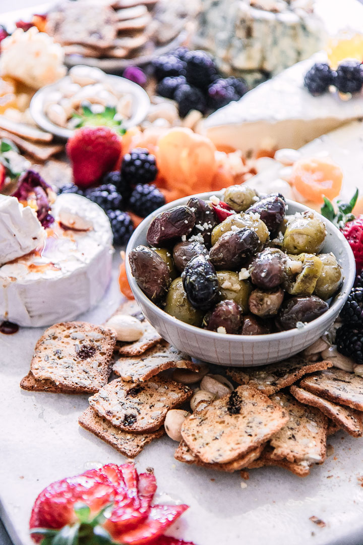 A bowl of olives on a cheese plate with crackers and berries.