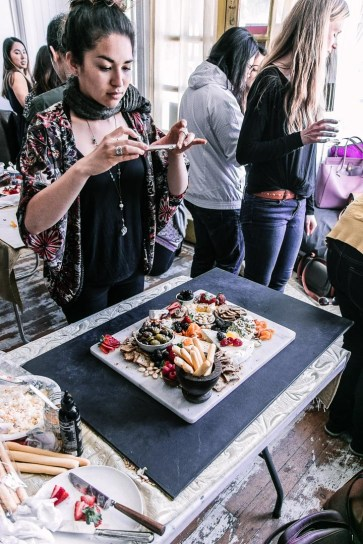 A woman taking a photo of a cheese plate at a food photography workshop.