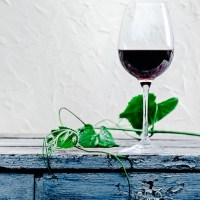 A glass of wine with a green vine on a blue dresser for the article 5 Foodie things to do in Valdosta Georgia.