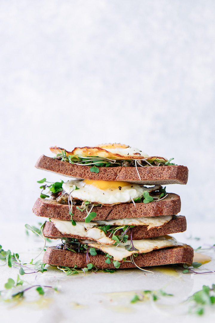 Stacked pieces of bread with olive tapenade, olive oil, microgreens, and sunny eggs on a piece of marble.
