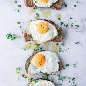 Four pieces of toast with olive tapenade, olive oil, microgreens, and a sunny egg on top of marble.
