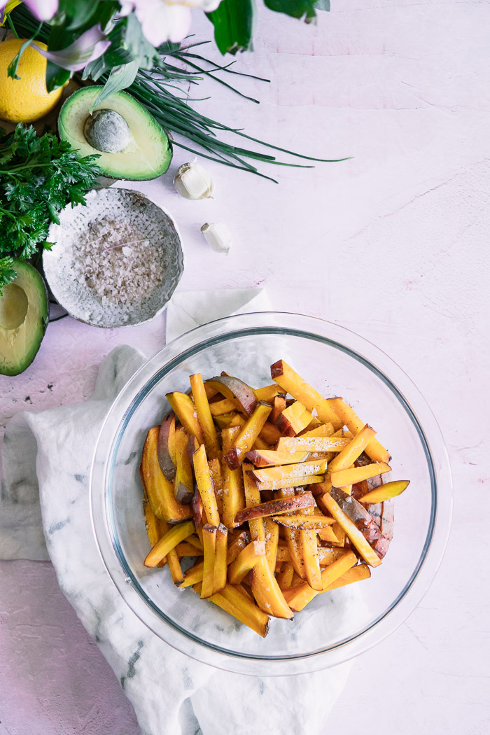 Cut golden beets in a bowl on a pink table with herbs and an avocado.