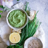 A white bowl with a bright green vegan dip on a blue table.