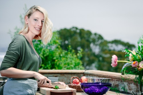 Kristina Todini, RDN of Fork in the Road cutting vegetables in an outdoor kitchen.