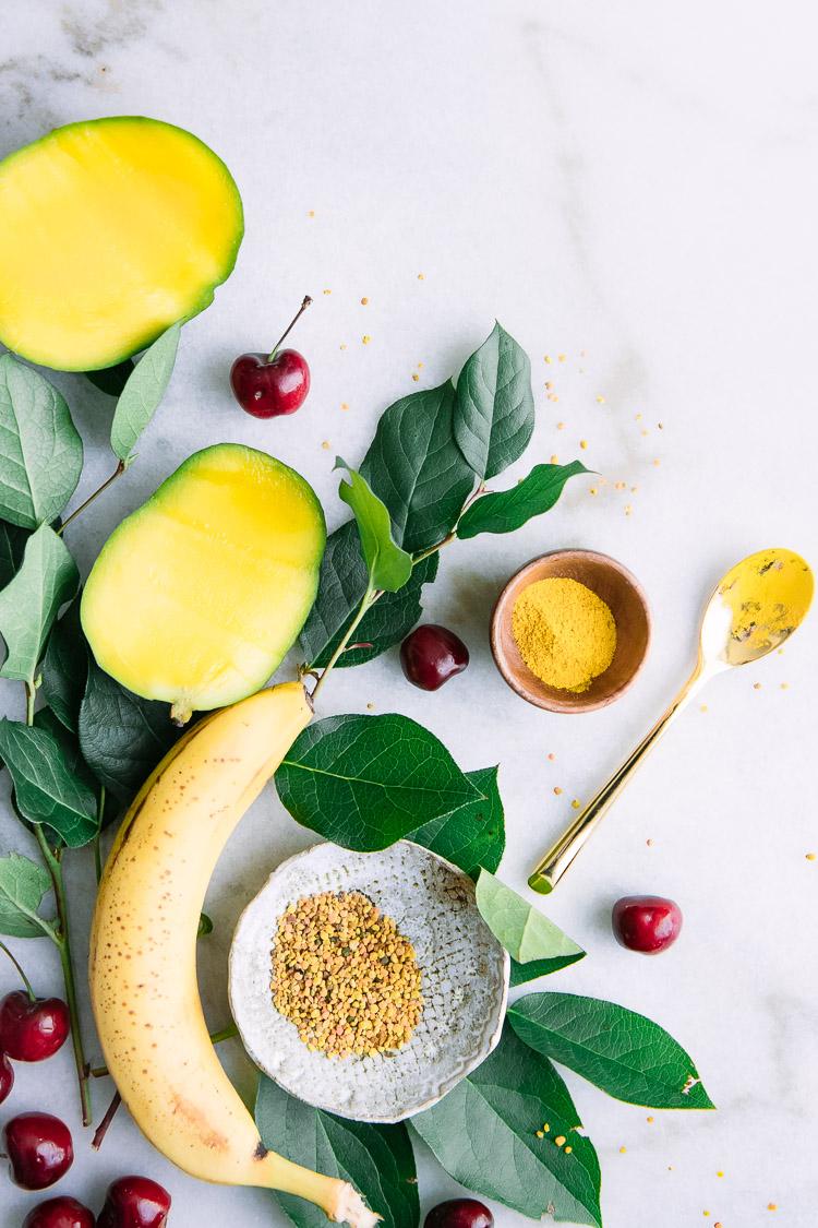 A flatlay of yellow superfoods including banana, mango, turmeric, bee pollen.