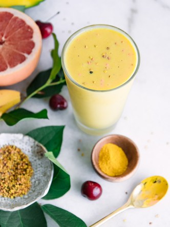 A mango banana pineapple yellow smoothie in a glass with bee pollen, turmeric, grapefruit, and bananas arrange around it on a white table.