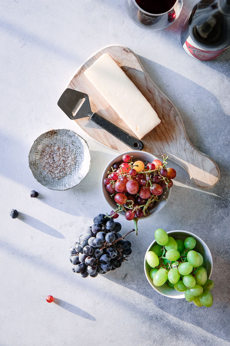 Bowls of red, green, and purple grapes with parmesan cheese on a cutting board and a dish of pink smoky salt.