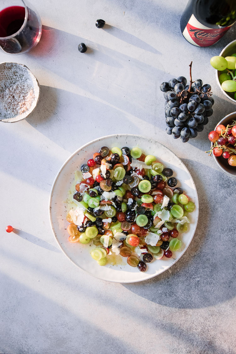 A grape and cheese fruit salad on a white plate on a white table with sunlight.