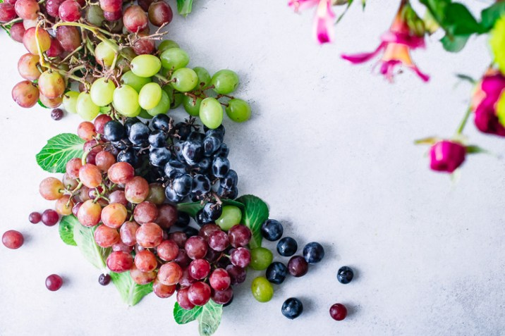 A bunch of colorful grapes on a counter with a bouquet of pink flowers.