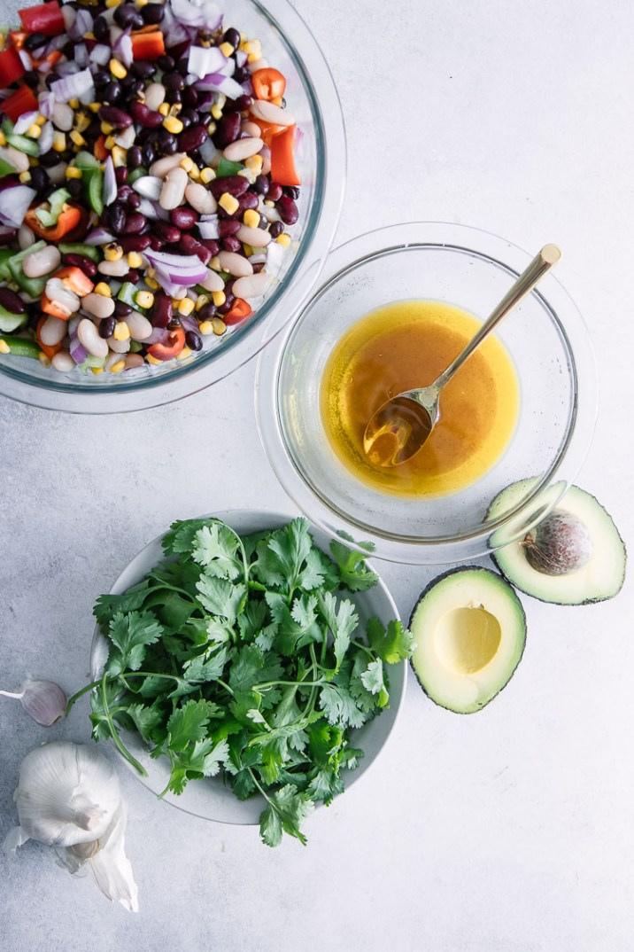 Ingredient flatlay for a mexican bean salad with olive oil, avocados, cilantro, and garlic on a blue table.