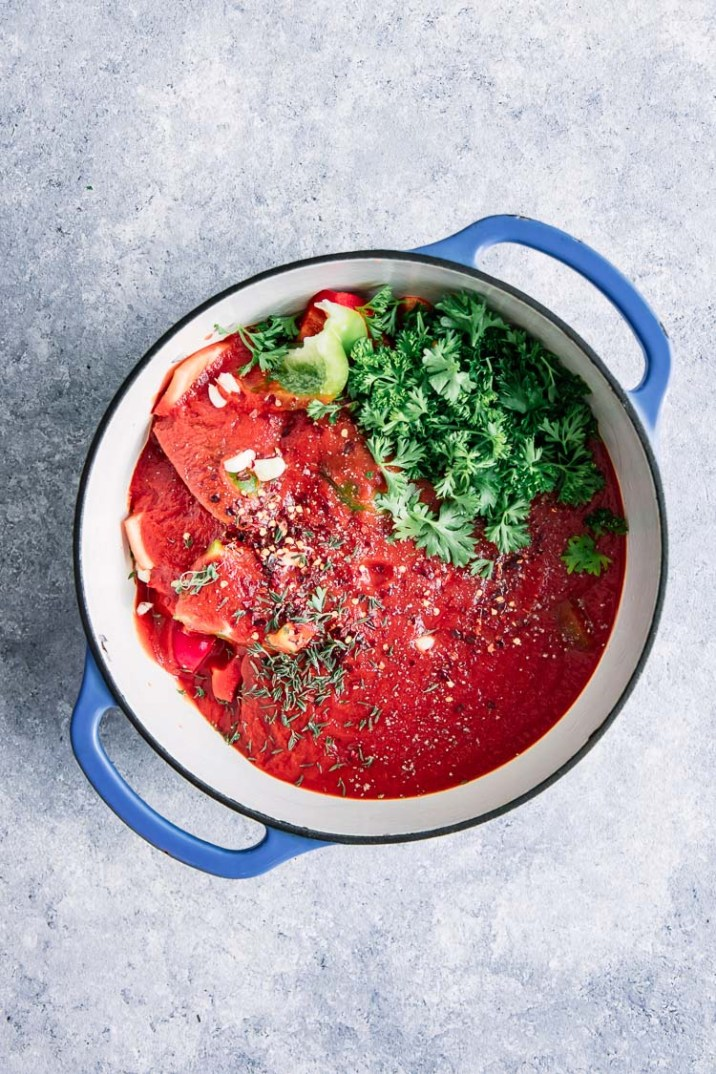 A soup pot of gazpacho with tomato, cucumbers, and herbs.