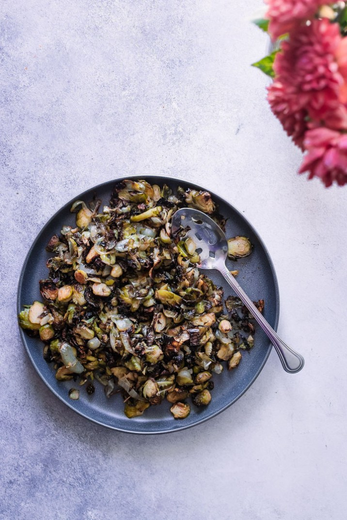 A blue plate with roasted brussels sprouts with kimchi on a blue table with pink flowers.