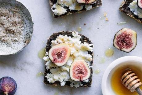 A piece of breakfast bread with cheese, figs, and honey on a table.