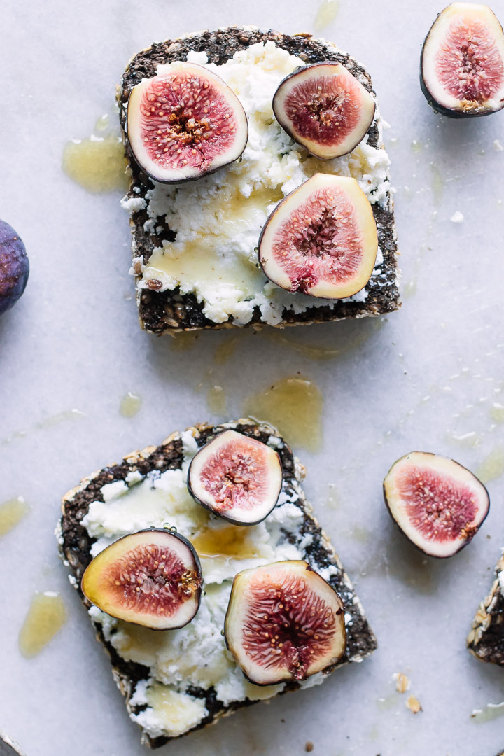 Wheat toast with ricotta cheese, figs, honey, and salt on marble.