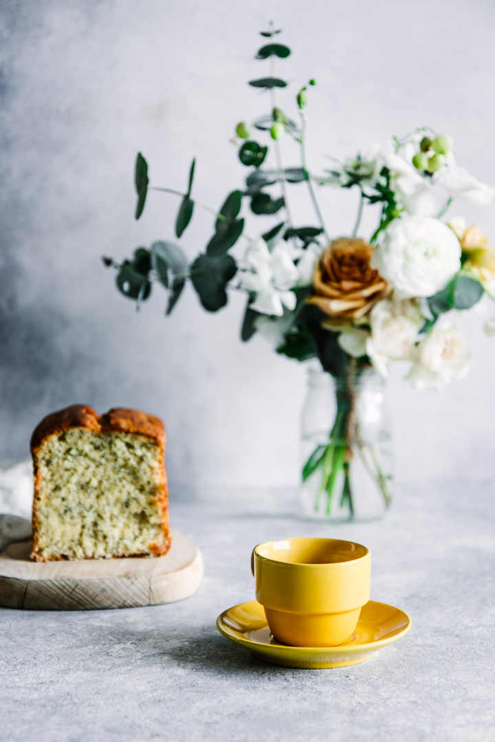 A cup of coffee and a piece of cake with a bouquet of flowers.