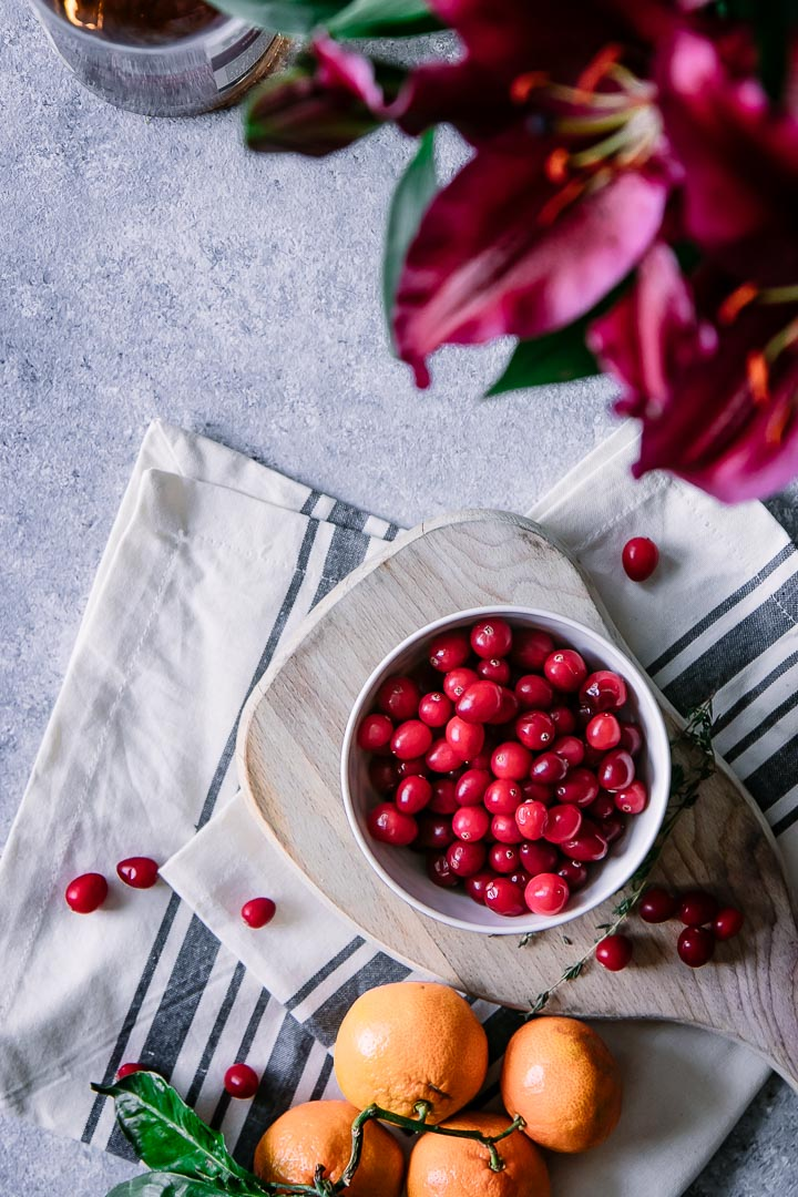 A bowl of cranberries on a table with flowers