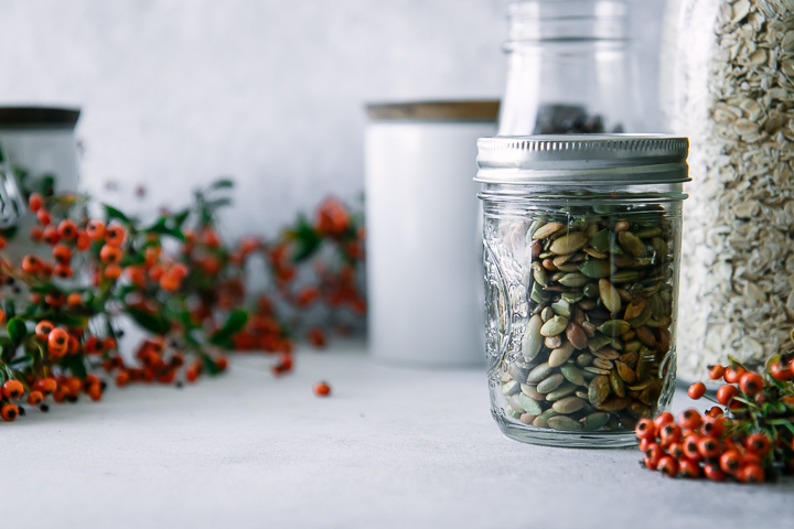 A jar of pumpkin seeds on a table with orange flowers