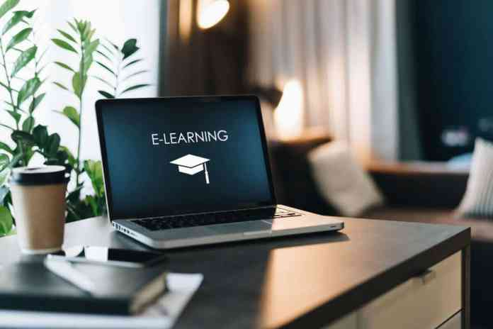 pc appoggiato su un tavolo e nella schermata è presente la scritta e-learning