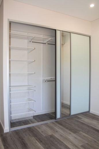 White Glass Sliding Doors Doors Granny Flat New Build, single mirror insert elfa shelving and silver mist plank floor boards