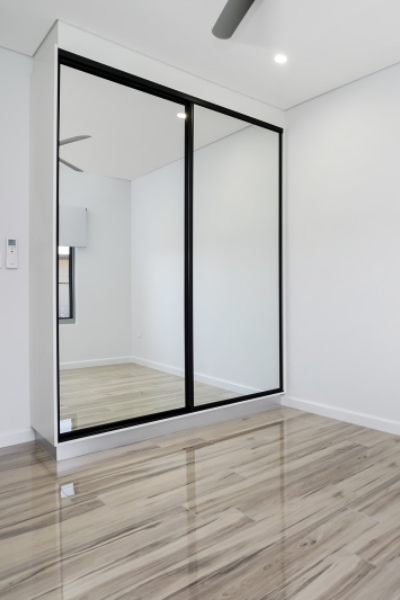 Territory Homes Mirror Sliding Doors with Black Frames