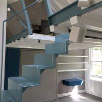 A blue steel truss mezzanine transforms a single storey cottage refurbishment.