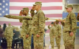"""FORT CARSON, Colo. — Col. Monté Rone, left, commander, and Command Sgt. Maj. Charles Tennant, senior enlisted adviser, 1st Stryker Brigade Combat Team, 4th Infantry Division, salute the flag during a formal ceremony while the national anthem is played at the William """"Bill"""" Reed Special Events Center Jan. 24, 2019. (Photo by Spc. Marcus McKinney)"""