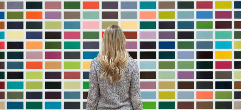 Woman standing in front of a mosaic of colors.