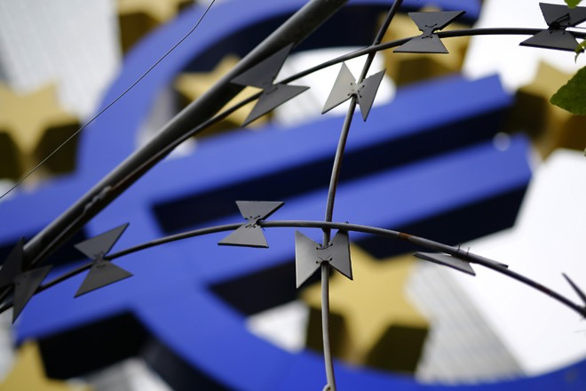 Protestors left some barbed wire in front of the euro sign landmark outside the headquarters of the ECB before its monthly news conference in Frankfurt