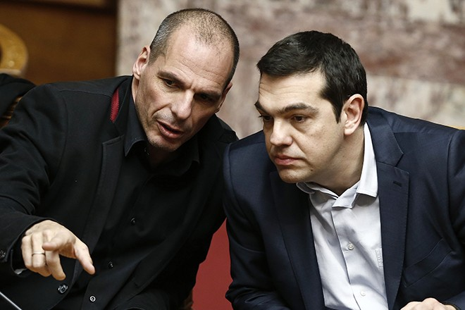 Greek Prime Minister Tsipras and Finance Minister Varoufakis talk during the first round of a presidential vote at the Greek parliament in Athens