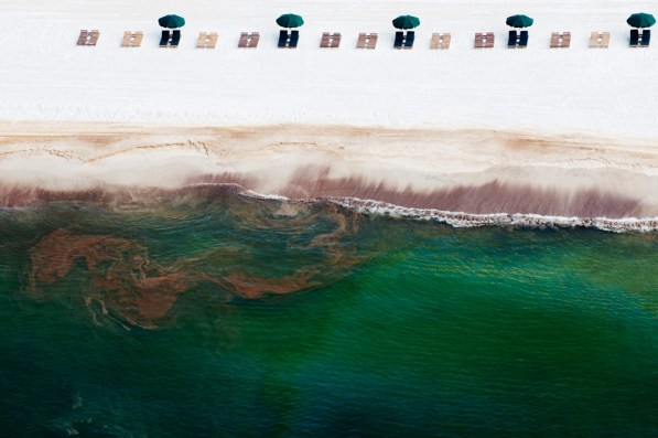 Empty beach chairs rest on the sand as oil washes ashore in Orange Beach, Alabama, U.S., on Saturday, June 19, 2010. The BP Plc oil spill, which began when the leased Transocean Deepwater Horizon oil rig exploded on April 20, is gushing as much as 60,000 barrels of oil a day into the Gulf of Mexico, the government said. Photographer: Kari Goodnough/Bloomberg