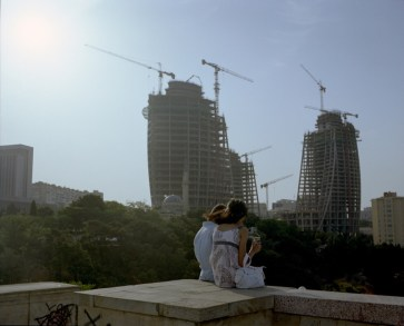 A couple in Kirov park, overlooking luxury construction project. Baku, Azerbaijan. 2010