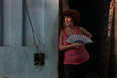 Woman outside her house watches people pass. Electrical cables are always run and connected outside the walls. Habana Vieja, November 2013.