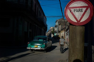 Man walking early morning in a typical deteriorated street of Centro Habana. November, 2013