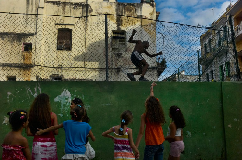 Girls playing and boy playing football the otherside of the wall. Boy is teasing the girls. Near Vedado an upscale neighborhood in Havana, November 2013.