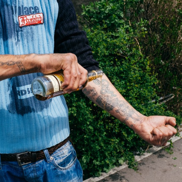 Gheorghe, a unemployed ex-con pours some liquor on his tatoos for 'his brothers still in prison.'