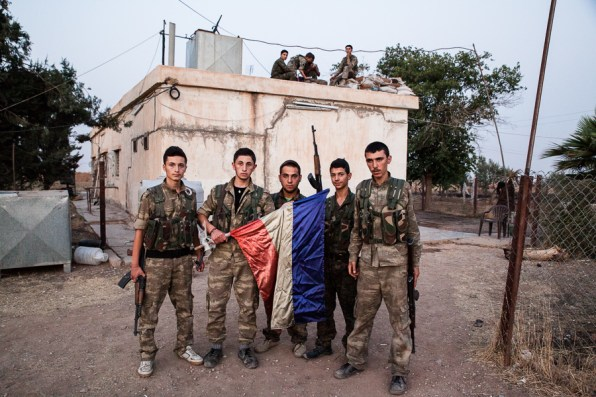 TSoldiers display the flag of the Syriac community reuniting Catholic and Orthodox Christians. South of Tirbespiyeh, Syria, June 2014