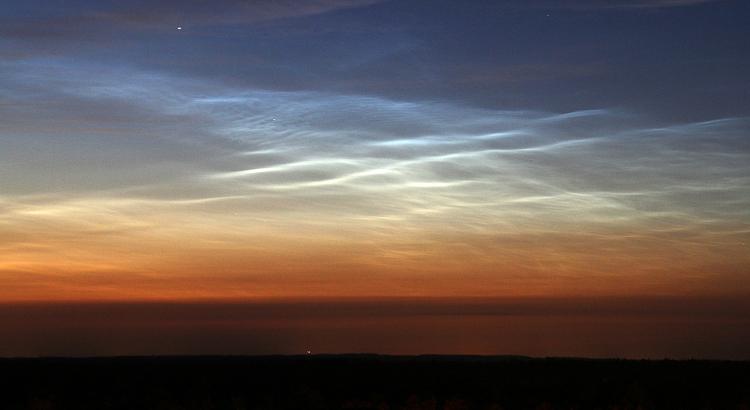 Golvende patronen in lichtende nachtwolken