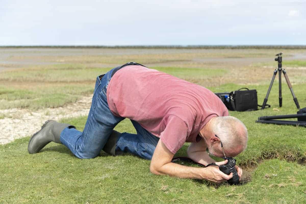 Deelnemer kruipt over de grond tijdens Groninger Waddenkust