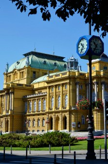 ZAGREB, CROATIA - 13 AUGUST, 2011: Side view of the Croatian national theater in Zagreb, Croatia and a blue public clock, another Zagreb landmark.