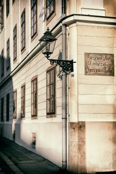 "Vintage style photo of an old lantern at the corner of the street. The street sign in old croatian and german laguages reads ""Gentlemans' Street""."