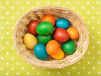 Colorful home-made organic easter eggs in a simple basket on a green background