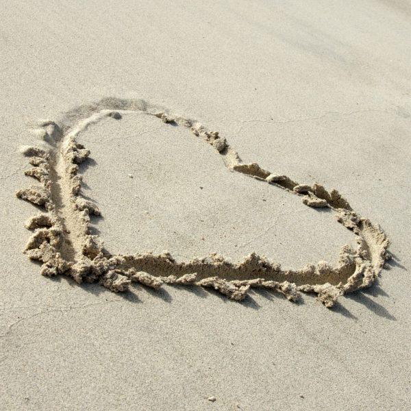 Symbolsk hjerte i sanden.