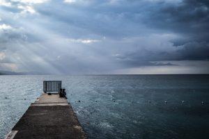 To mennesker sittende ytterst på en pier i Montego Bay på Jamaica i det solen bryter gjennom skylaget.