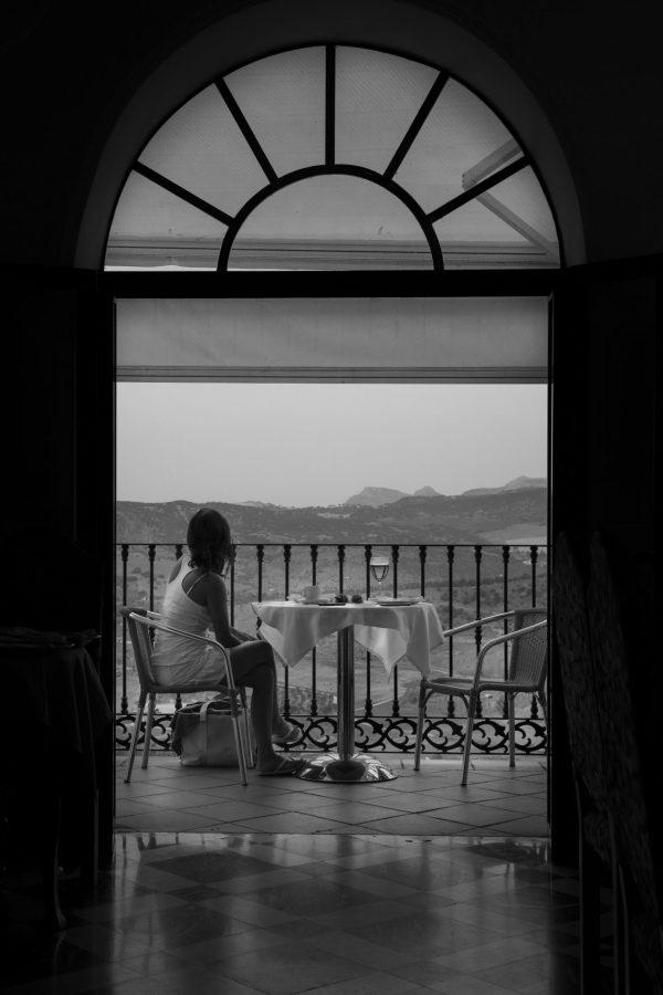 Enslig og velkledd kvinne nyter utsikten til dalen nedenfor Ronda i Andalucia, Spania.