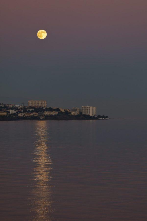 Fullmåne på vei opp over Costa del Sol i Spania. Himmelen og havet speiles av deilige pastellfarger.