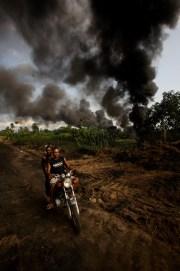 """George Osodi Smoking Pipe, 2007 dalla serie """"Oil Rich Niger Delta"""" stampa digitale, 119 x 79 cm © l'artista, courtesy Fondazione Cassa di Risparmio di Modena"""