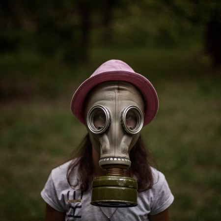 10 years old Ukrainian girl puts on a gas mask during training in Lider summer camp outskirts, Ukrain, 2018