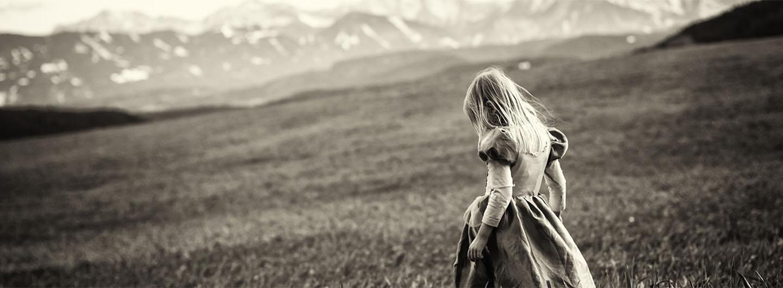 Mädchen auf Wiese vor einer Bergkulisse.