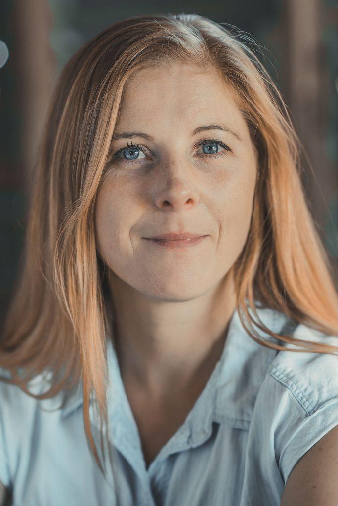 Frau mit langen dunkelblonden Haaren und bauen Hemd